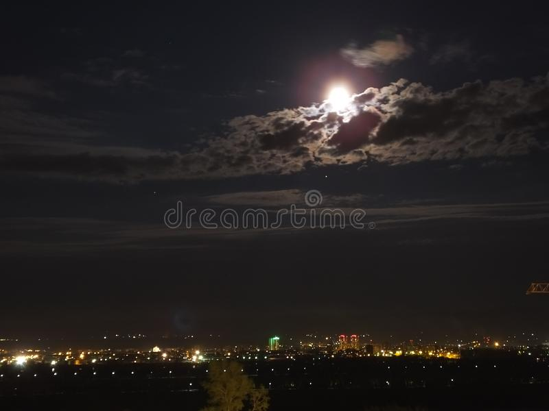 City at night with moon on sky. City at night with moon in the sky royalty free stock image
