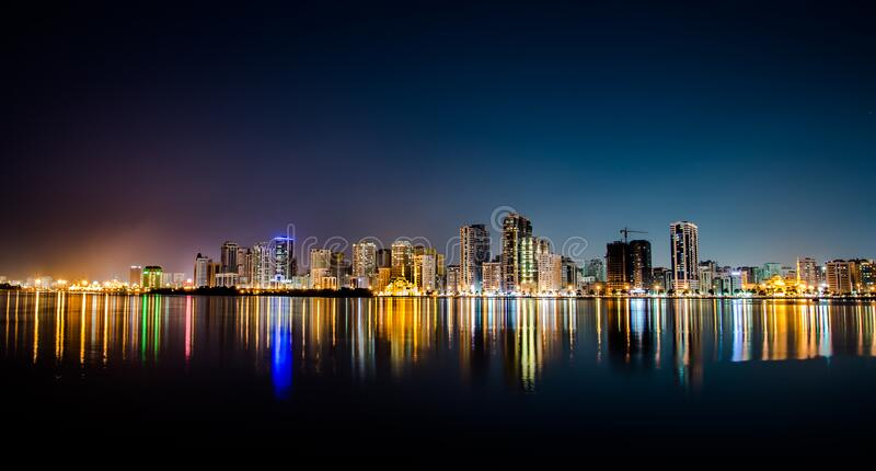 City at night reflected on ocean stock photography