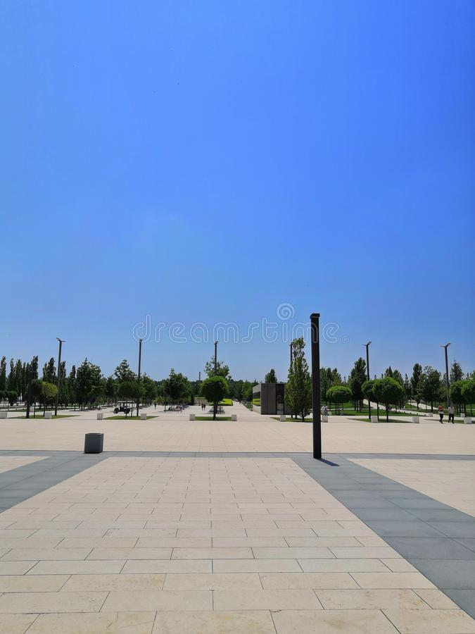 City Park blue sky, tiles, lights, trees background. The track is lit by modern street lights. City Park blue sky, tiles, lights, trees background. The figure royalty free stock photo