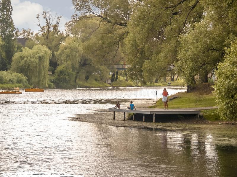 City park with lake. Children playing on the pier royalty free stock photo