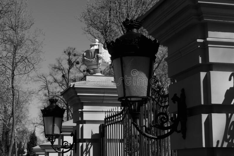 In a city park with sculptures, lanterns cast their shadow on the fence. In a beautiful city park near the palace with beautiful sculptures, wall lights cast a stock photos
