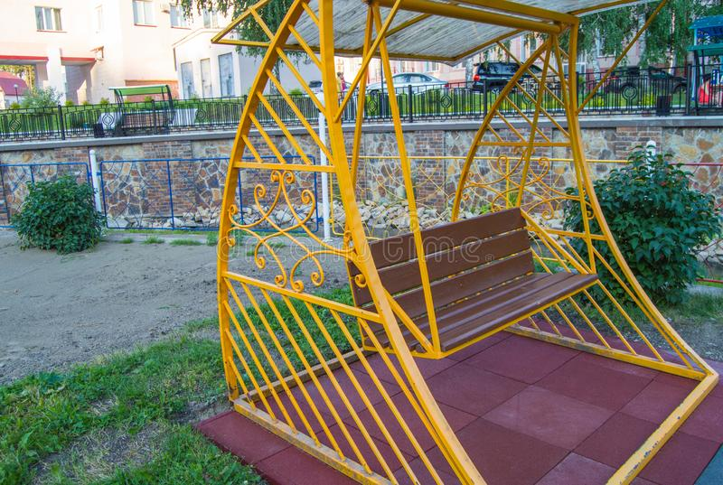 City Park in summer, empty wooden swing with yellow decorative metal frame, outdoor leisure furniture stock image