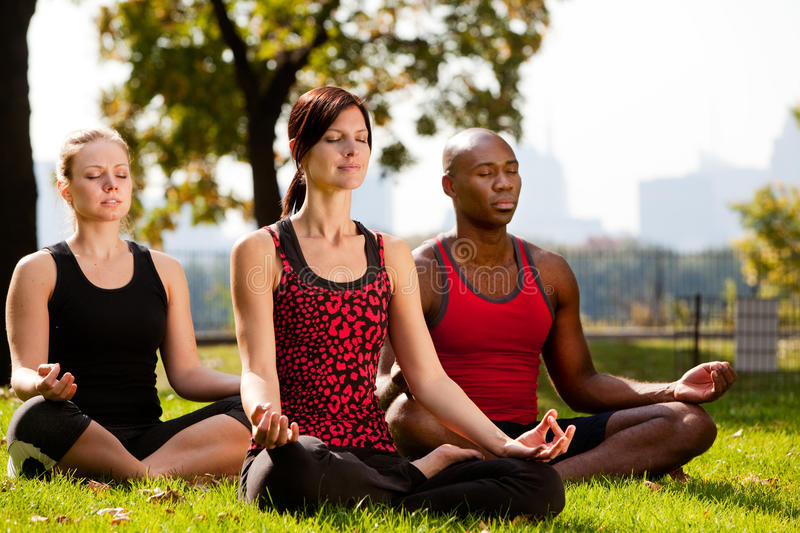 City Park Yoga. A group of people doing yoga in a city park royalty free stock photo
