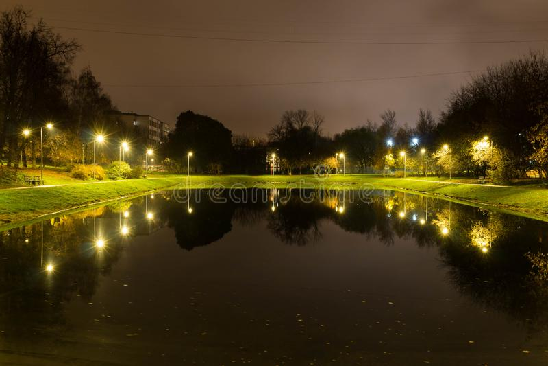 City pond with illumination around the radius with the reflection of lights stock photo
