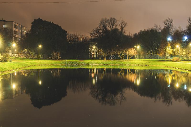 City pond with illumination around the radius with the reflection of lights stock image