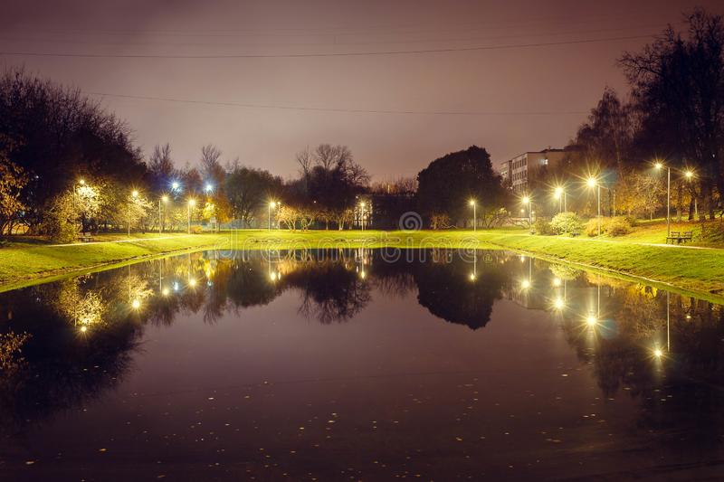 City pond with illumination around the radius with the reflection of lights royalty free stock photography
