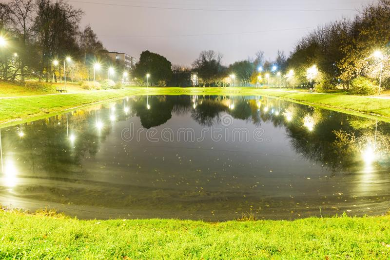 City pond with illumination around the radius with the reflection of lights royalty free stock images