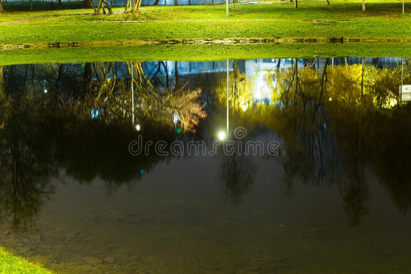 City pond with illumination around the radius with the reflection of lights royalty free stock image