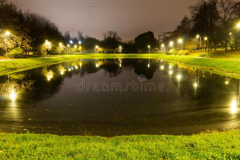 City pond with illumination around the radius with the reflection of lights royalty free stock photos