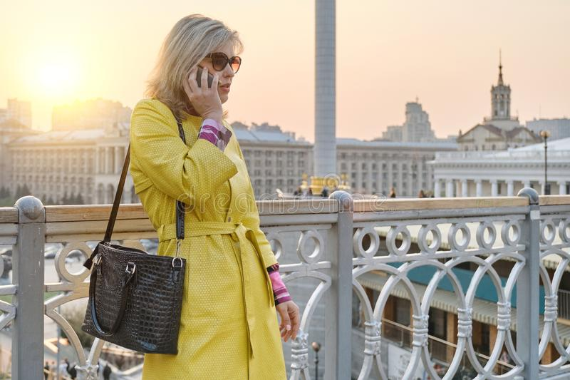 City portrait of mature smiling woman in glasses, yellow coat talking on mobile phone, background urban panorama, copy space royalty free stock images