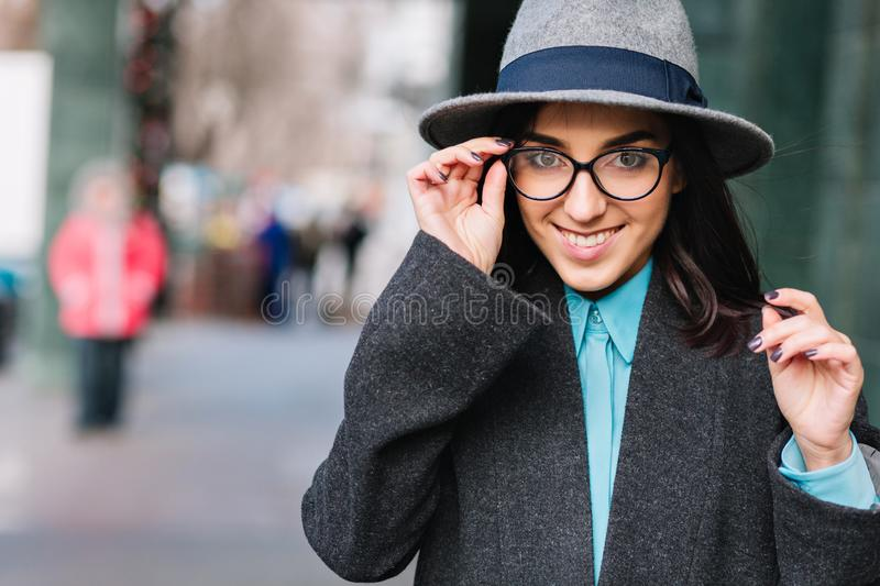 City portrait stylish charming young woman in grey coat, hat walking on street. Modern black glasses, smiling stock image