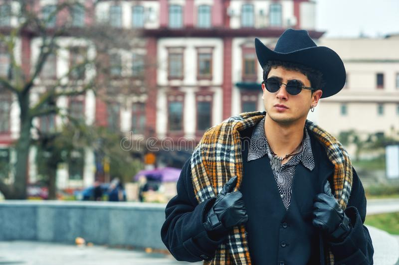 City portrait of a young man in a dark coat and hat royalty free stock images