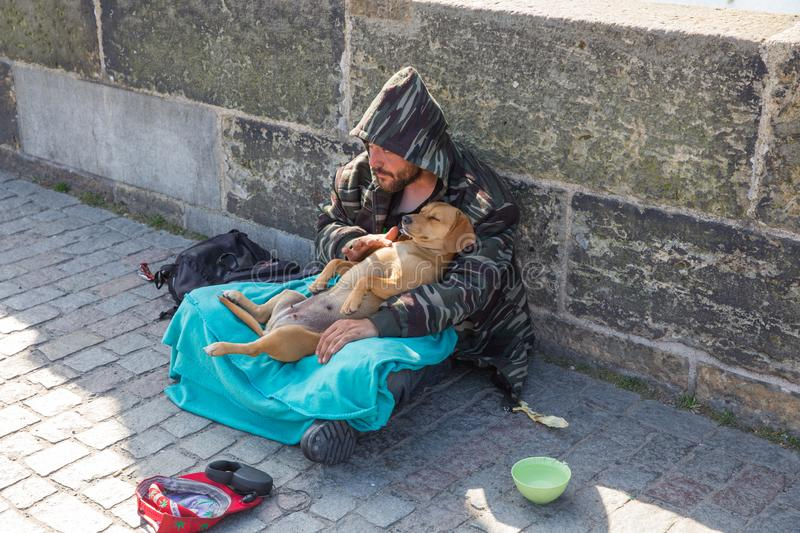 City Prague, Czech Republic. On the street the beggar with dog treats people for money. 2019. 24. April royalty free stock photos