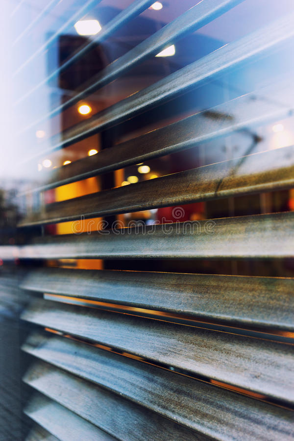 The city is reflected in the window of a cafe with shutters royalty free stock photos