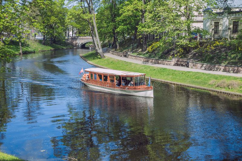 City Riga, Latvia Republic. Tourists on a boat ride through the city canal. Around the trees and nature. May 7. 2019 Travel photo royalty free stock photos
