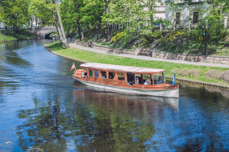 City Riga, Latvia Republic. Tourists on a boat ride through the city canal. Around the trees and nature. May 7. 2019 Travel photo royalty free stock photo