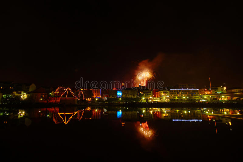 City By River At Night, Maribor, Slovenia. Night view of historic quarter of Lent in Maribor by the Drava river with medieval Water tower, new modern City hotel royalty free stock images