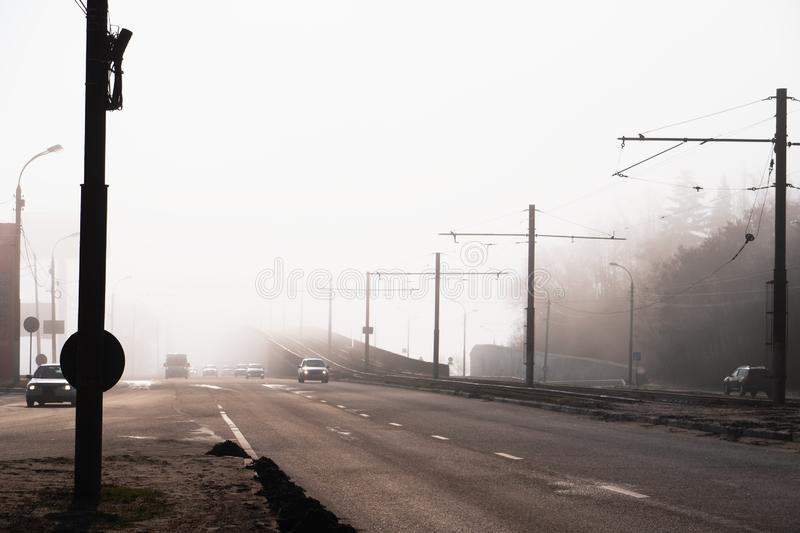 City road or street with car traffic in morning spring fog or haze, atmospheric urban photo.  royalty free stock photo
