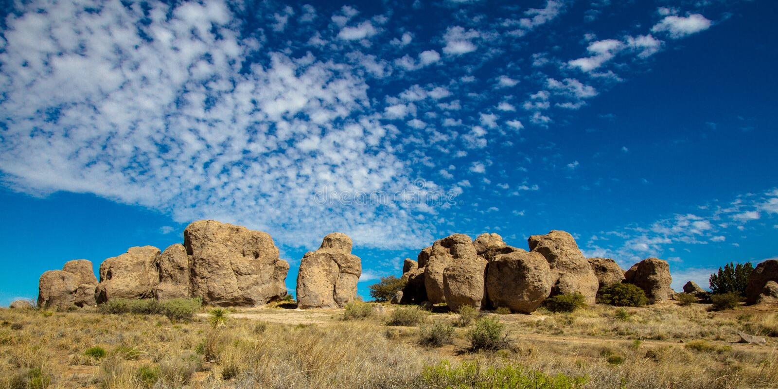 Wide view including beautiful clouds at City of Rocks State Park near Silver City, New Mexico. Enormous boulders and beautiful clouds at City of Rocks State Park royalty free stock photo