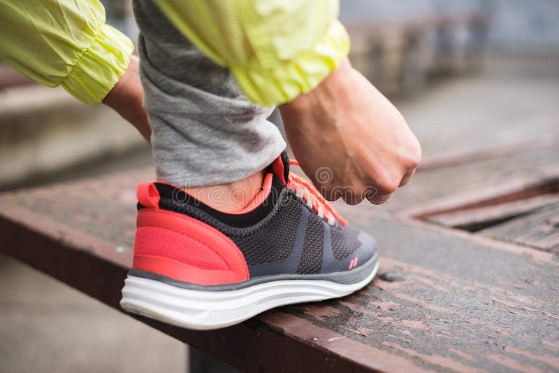 City runner lacing sport footwear. Female runner tying sport shoes laces before running urban challenge. Sporty unrecognizable woman lacing footwear getting royalty free stock images