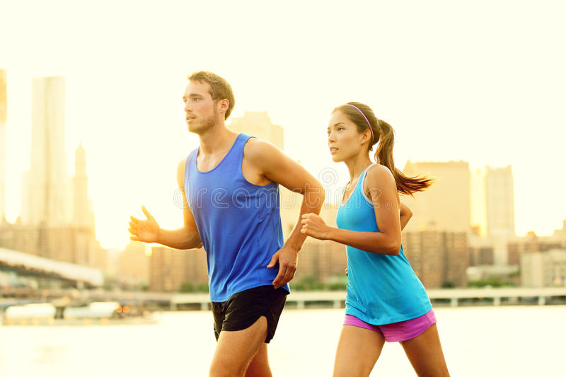 City running couple jogging outside. Runners training outdoors working out in Brooklyn with Manhattan, New York City in the background. Fit multiracial fitness stock image