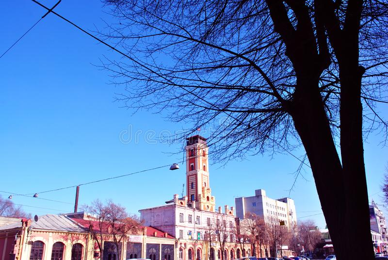 City scape with 19th century fire department pink tower, against a background of a spring blue sky and dark tree silhouette. Foreground stock photos