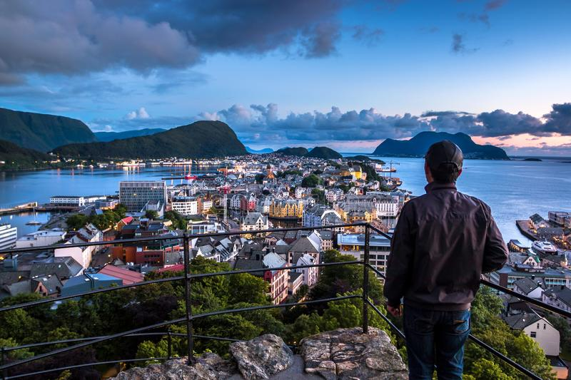 City Scene with A Lone Man Overlooking Alesund Center at Night. Image of Alesund after midnight in Summer taken from Mount Aksla Viewpoint. Alesund is a port royalty free stock images
