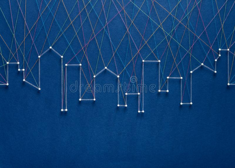 City skyline connection concept. Urban connection concept. Network of pins and threads in the shape of a city skyline symbolising urban diversity and royalty free stock images
