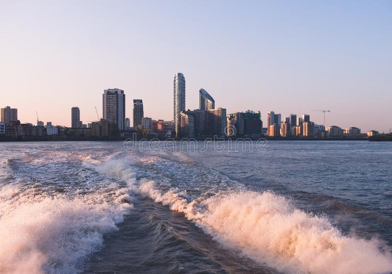 City skyline of London Docklands Canary Wharf seen from a boat royalty free stock photography