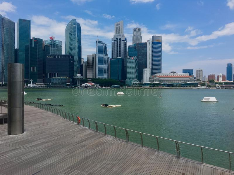 City skyline of modern Singapore. This picture is taken from outside of The Shoppes at Marina Bay Sands building on the wooden plank platform overlooking the bay stock image