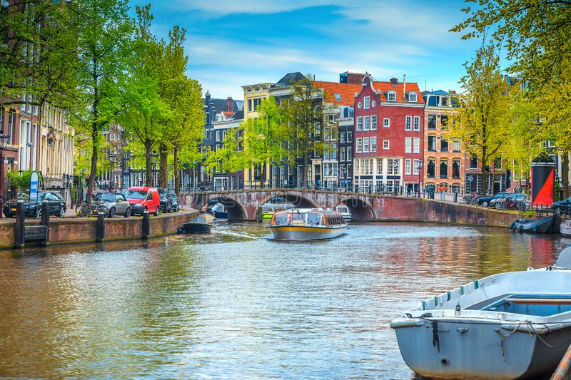 City skyline with water canal and tourist boats, Amsterdam, Netherlands stock photography