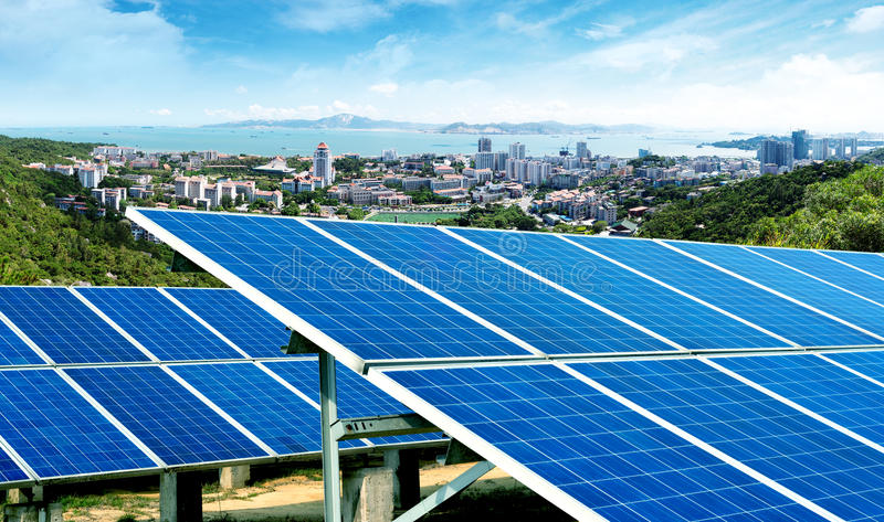 City skyline, Xiamen, China. Solar panels in front of the city skyline, Xiamen, China stock photo
