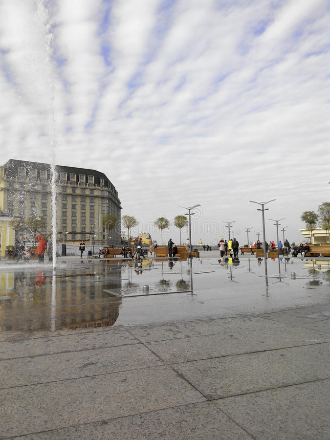 City square with fountains under cloudy sky stock photo