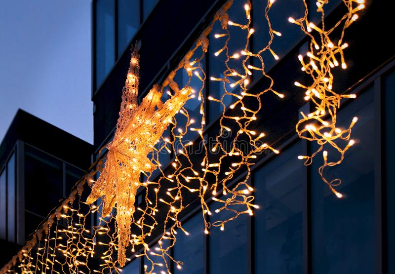 City street Christmas decoration. electric garlands with big North Star on the background of the facade of a modern building. At the dark. The star glows in royalty free stock image