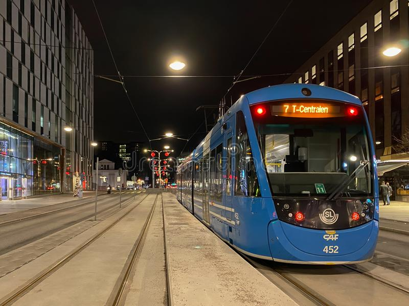 City street night view of a blue SL tram with incidental people in the background in Stockholm. STOCKHOLM, SWEDEN - DECEMBER 23, 2019: Perspective city street stock photography