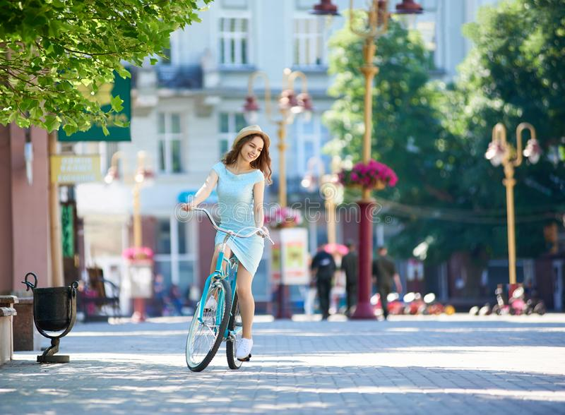 City street on summer day. Graceful girl rides bicycle. City street on a summer day. A graceful girl rides a bicycle. Retro bicycle in one tone with a girl`s royalty free stock image