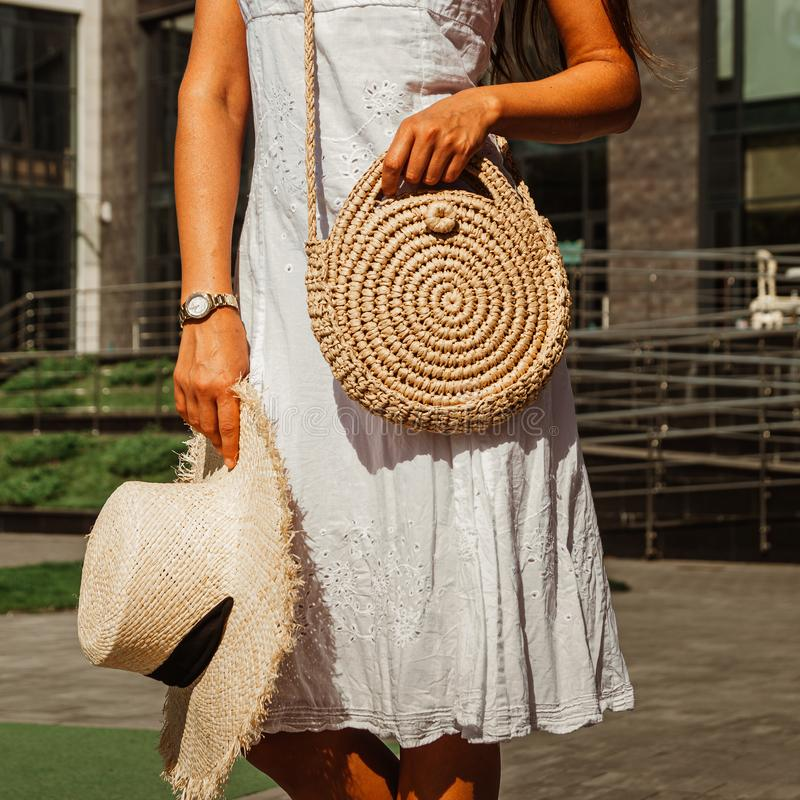 Slender girl in a white chintz dress holds a woven straw round bag in her hands stock photos