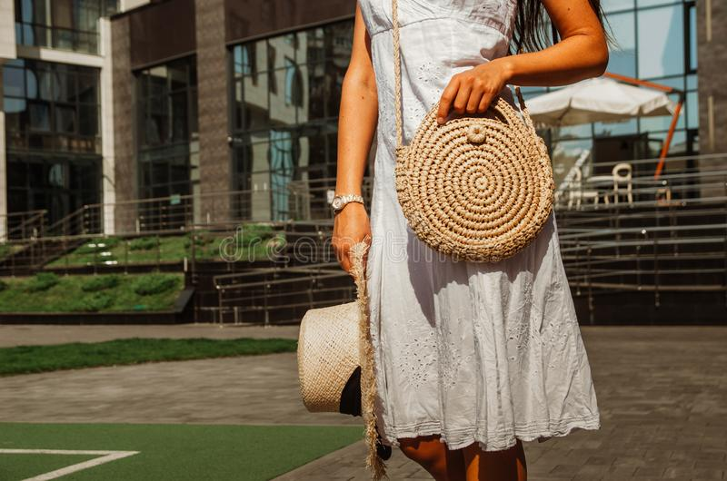 Slender girl in a white chintz dress holds a woven straw round bag in her hands stock photography