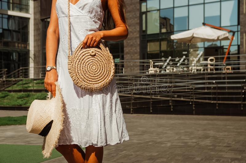 Slender girl in a white chintz dress holds a woven straw round bag in her hands stock image