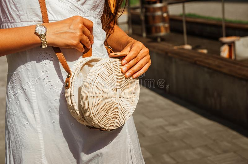Slender girl in a white chintz dress holds a woven straw round bag in her hands stock photo