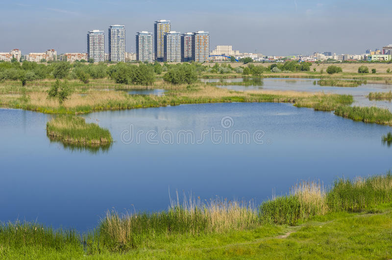 Bucharest Lake Vacaresti. City suburbs with ecosystem Vacaresti Lake near south-eastern Bucharest with tall residential buildings on May 7, 2014 in Bucharest stock photo