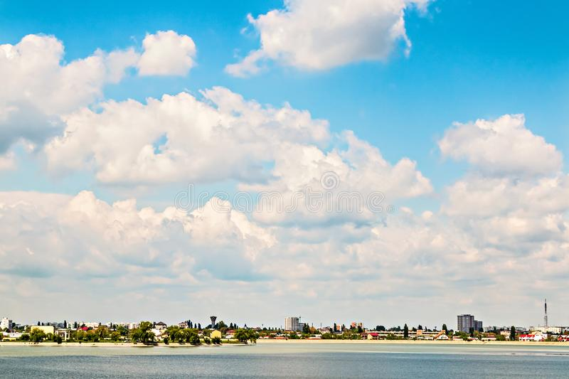 City summer landscape near lake cloudy sky. Panoramic city in summer landscape with houses and buildings by the water on the shore of the lake in Bucharest Lacul