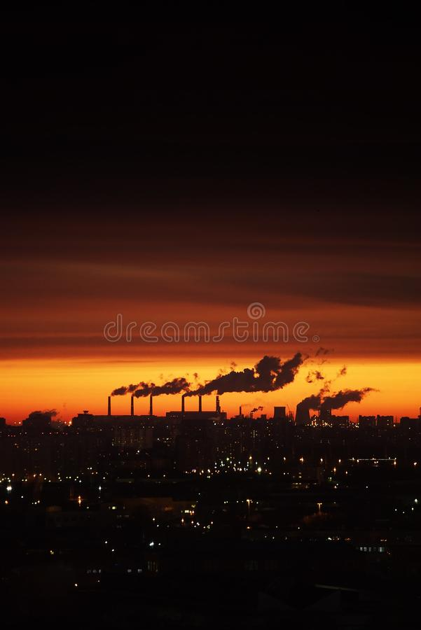 City at sunset. The outline of the buildings and smoking chimneys royalty free stock photography
