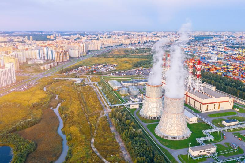 City thermal power station close to massive residential areas in the evening before sunset, aerial view stock photo