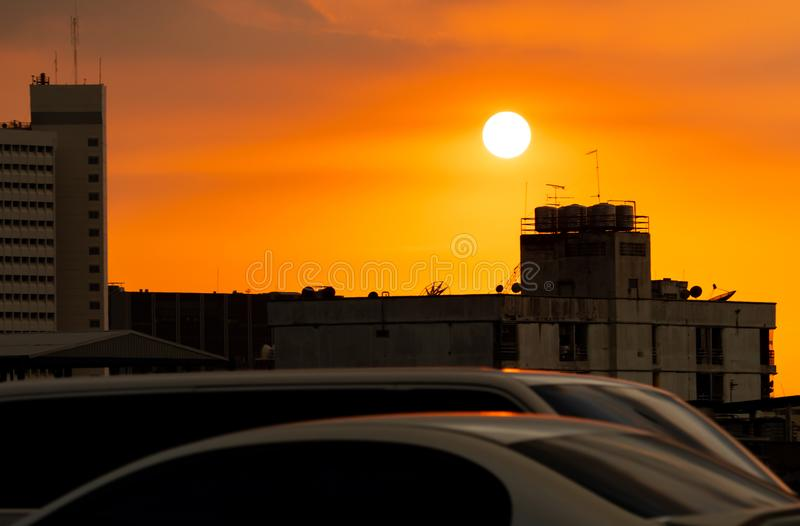 City and traffic jam in the evening with beautiful orange sunset sky. Concrete residential building in urban area. Silhouette. Transport on traffic jam near royalty free stock photography