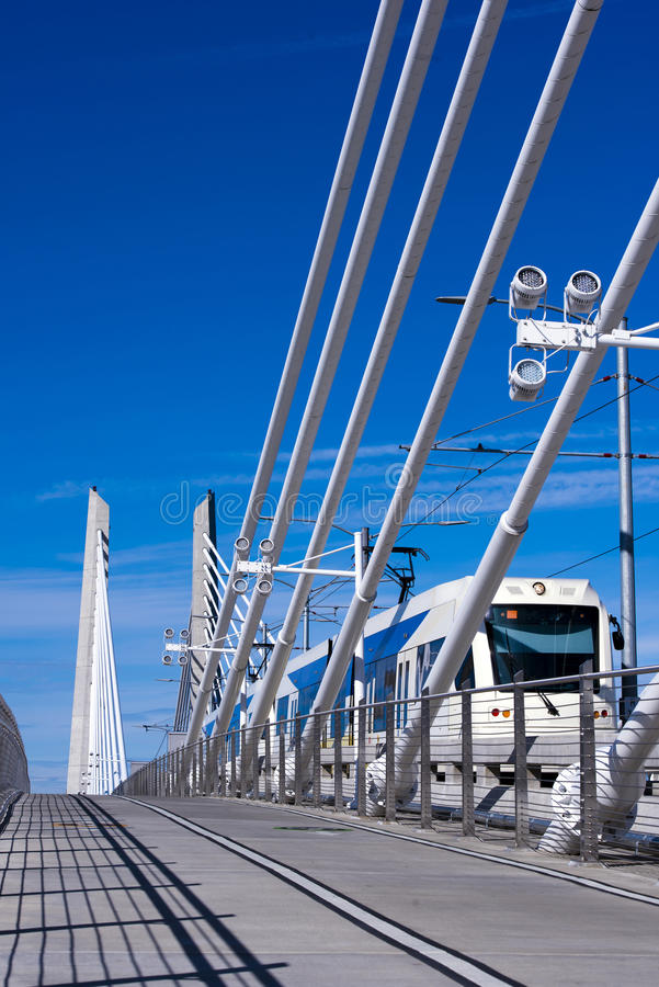 City tram on modern bridge in Portland. Modern city tram runs along the bridge with cable extensions Willamette across the river in Portland with a shadow from stock images