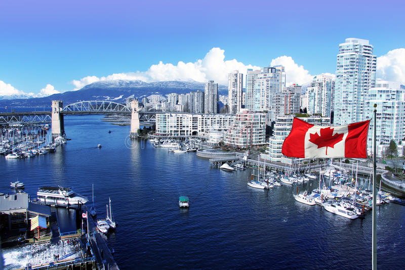 City of Vancouver. Canadian flag in front of view of False Creek and the Burrard street bridge in Vancouver, Canada royalty free stock photography