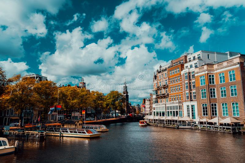 City view of Amsterdam with cruise boats and typical brick houses on sunny day with Vibrant fluffy clouds royalty free stock photography