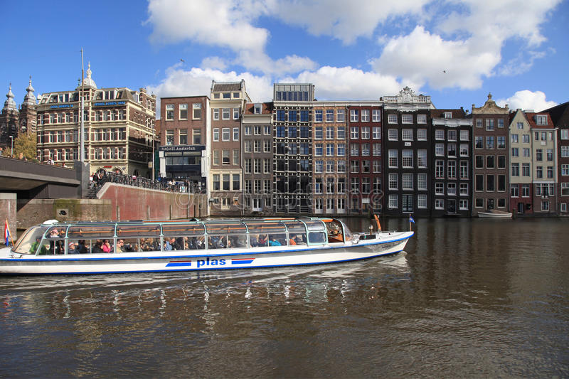 City view of canals, dutch houses and tour boat, Amsterdam, Netherlands. stock image