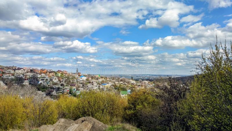 City view of the many small houses located on the hill. Blue sky with lots of clouds. Trees and shrubs in the foreground royalty free stock photo